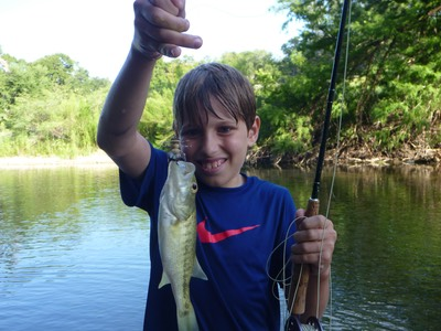 Boy learning to wade and fly fish on the Guadalupe River holding a bass.